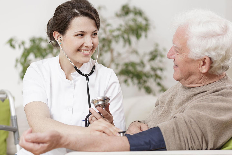 Ein Gesellschafter von Vitanova in Hamburg misst den Blutdruck eines lächelnden älteren Herren