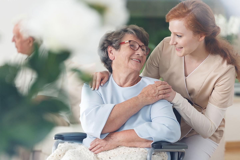 Ältere Dame im Rollstuhl legt ihre Hand auf die Hand der ambulanter Pflegerin von Vitanova Hamburg