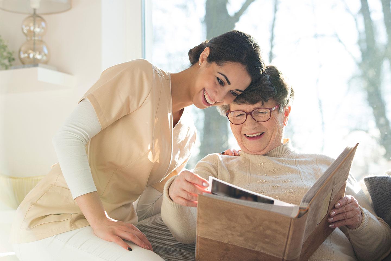 Eine alte Dame und ein lachender Gesellschafter von Vitanova Hamburg schauen zusammen ein Fotoalbum an