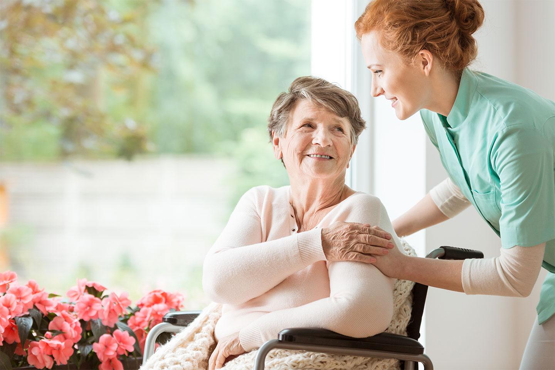 Ein Gesellschafter vom Pflegedienst Vitanova Hamburg lächelt eine älteren Dame im Rollstuhl zu